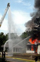 Firefighters shooting water at burning house with hoses and cranes
